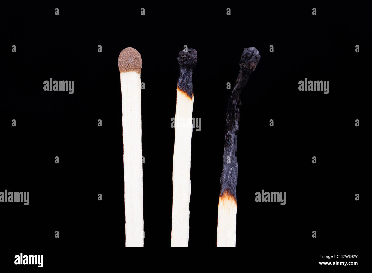 One healthy and two burnt matches in row, isolated on dark background. - Stock Image