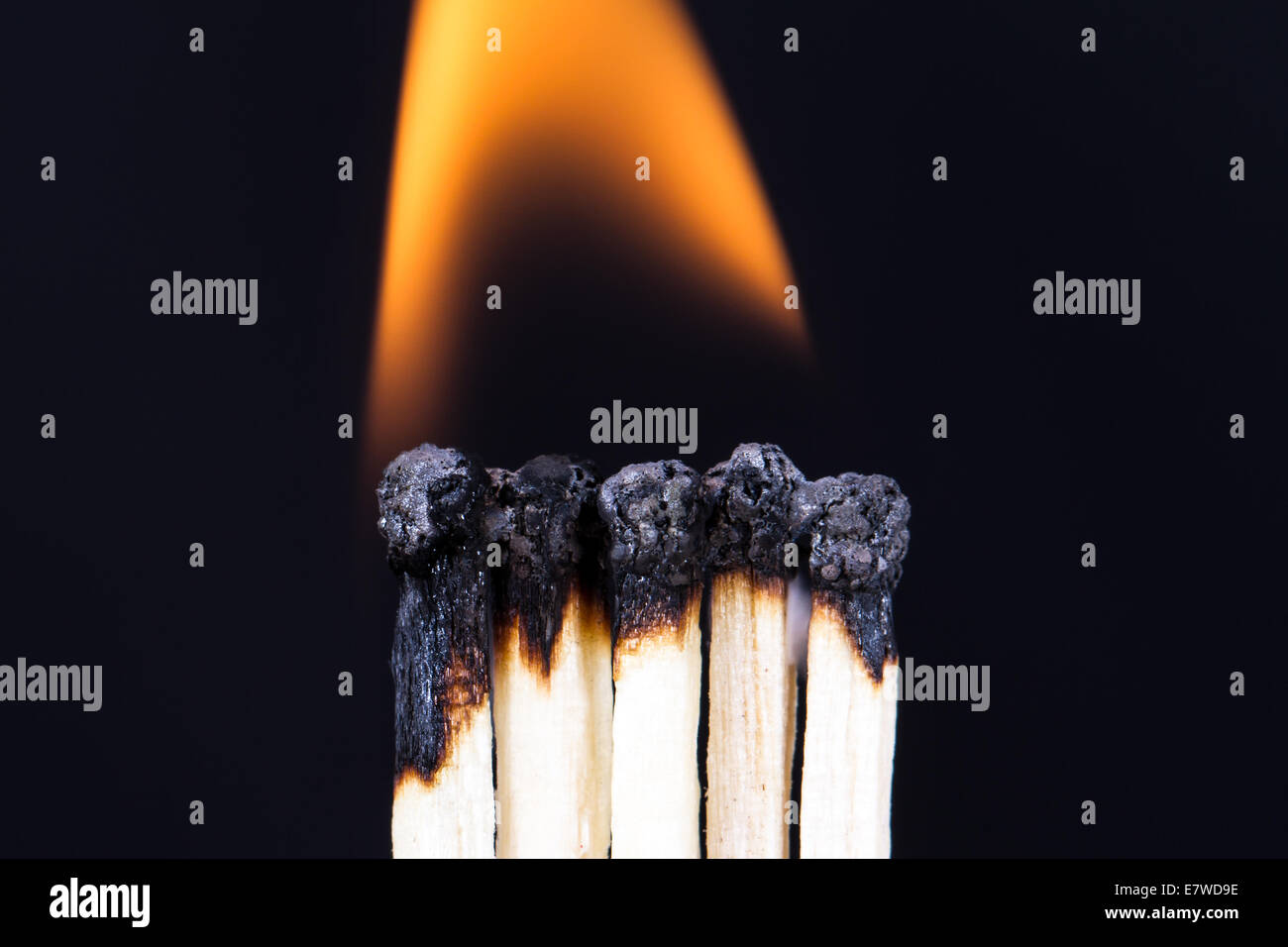 Teamwork concept, burning matches with flame on dark background. - Stock Image