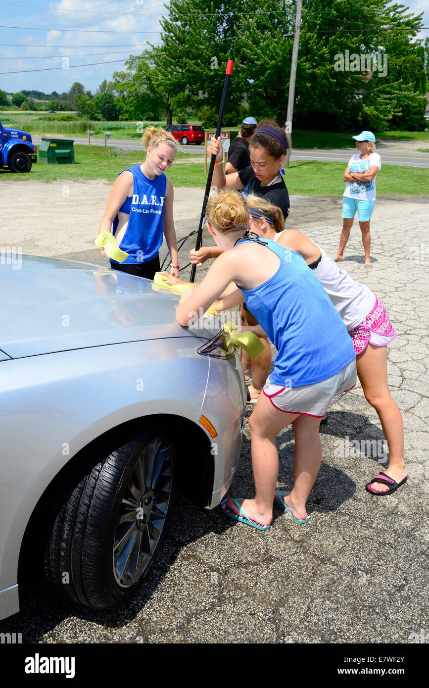 High school students wash cars to for fund raiser Stock