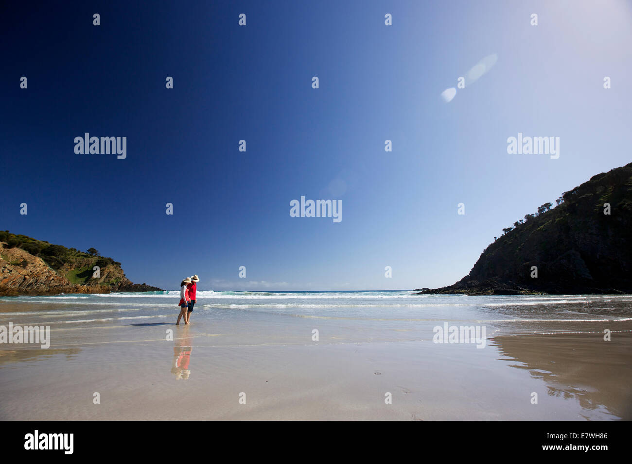 A couple walking along a private beach, on holiday, Snug Cove, Kangaroo Island, South Australia - Stock Image