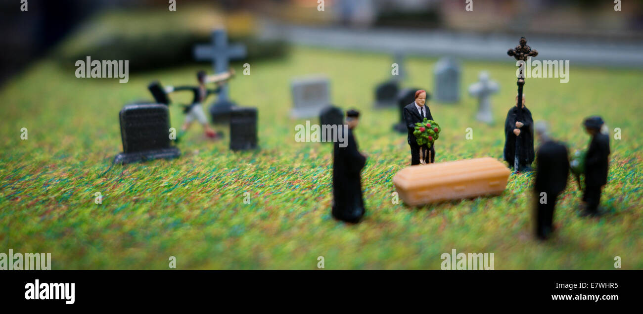 Tiny HO scale figure people mourn at a funeral scene. - Stock Image