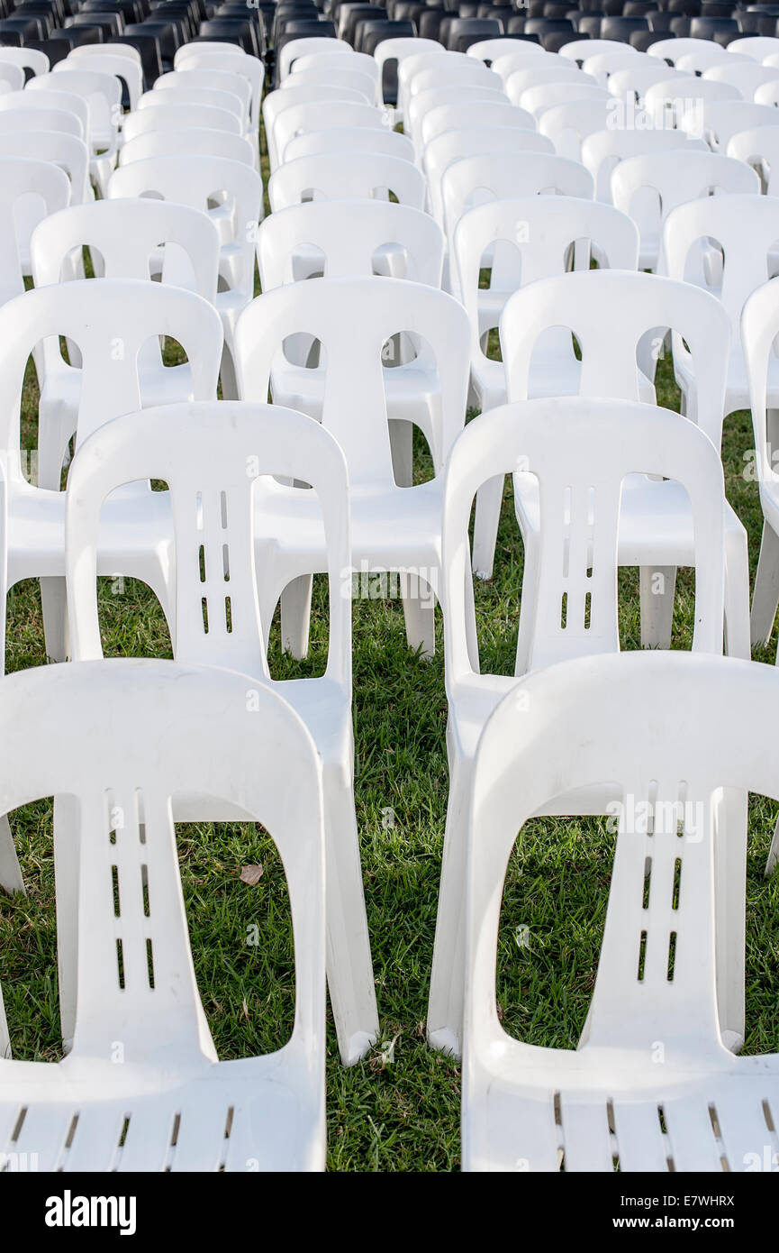 White Plastic Stackable Lawn Chairs In Rows Waiting For A Crowd
