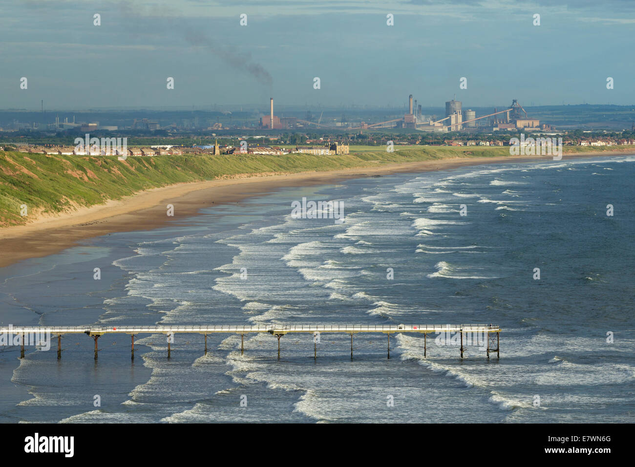 View over Saltburn pier and beach with Redcar Steelworks in distance. Saltburn by the Sea, North Yorkshire, England, Stock Photo
