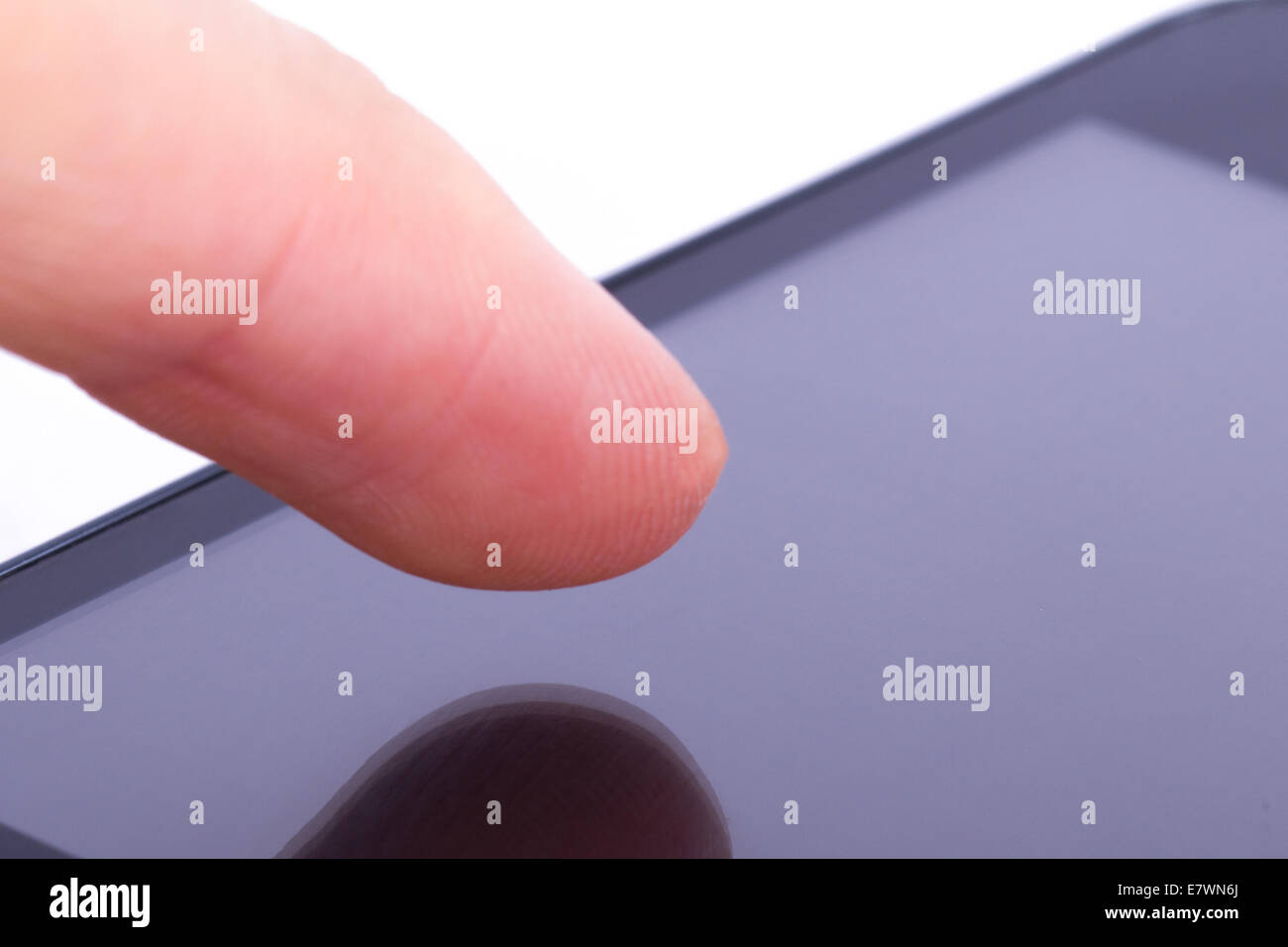 Finger touching blank mobile phone screen on white background. Stock Photo