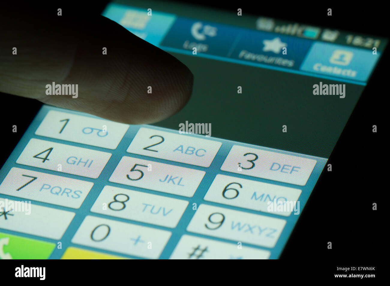 Finger touching dialing numbers on dark. - Stock Image