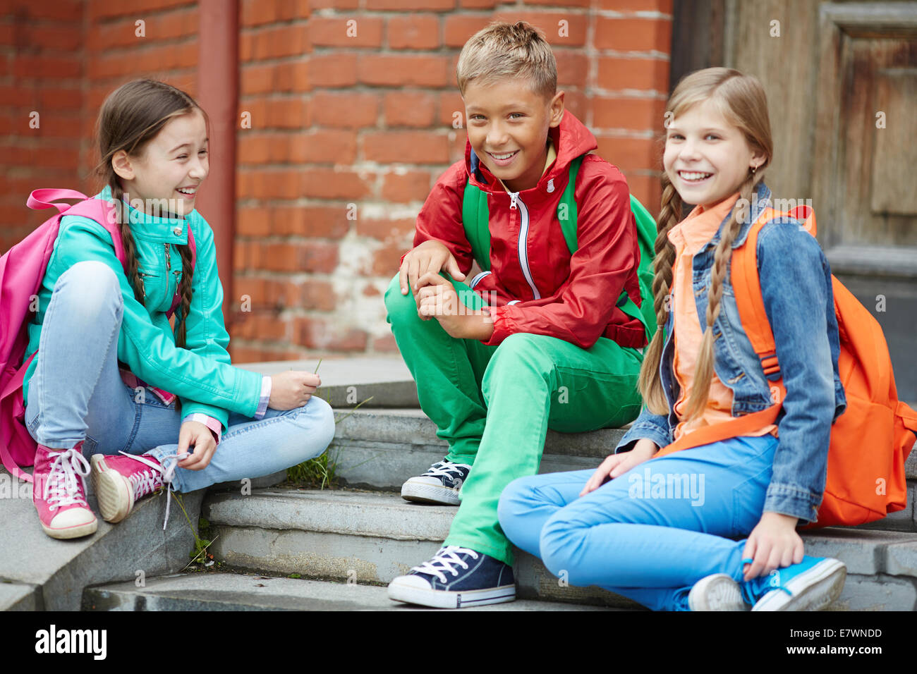 Happy schoolkids in casual enjoying time after school - Stock Image