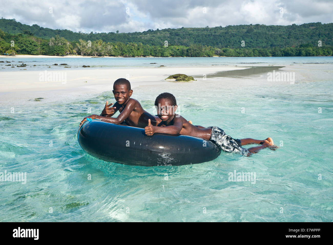 Two boys playing in the clear water, Espiritu Santo, Vanuatu - Stock Image