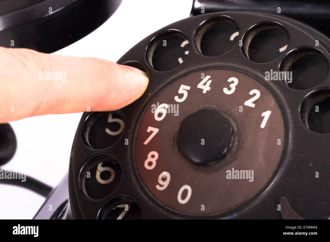 Close up view, hand finger on rotary dial of black vintage phone, isolated on white background. - Stock Image