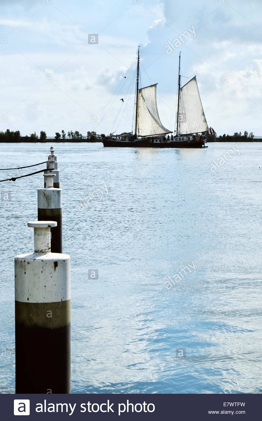 A gaff-rigged ketch leaves Enkhuizen's harbor to sail on the IJsselmeer, part of the body of water once known - Stock Image