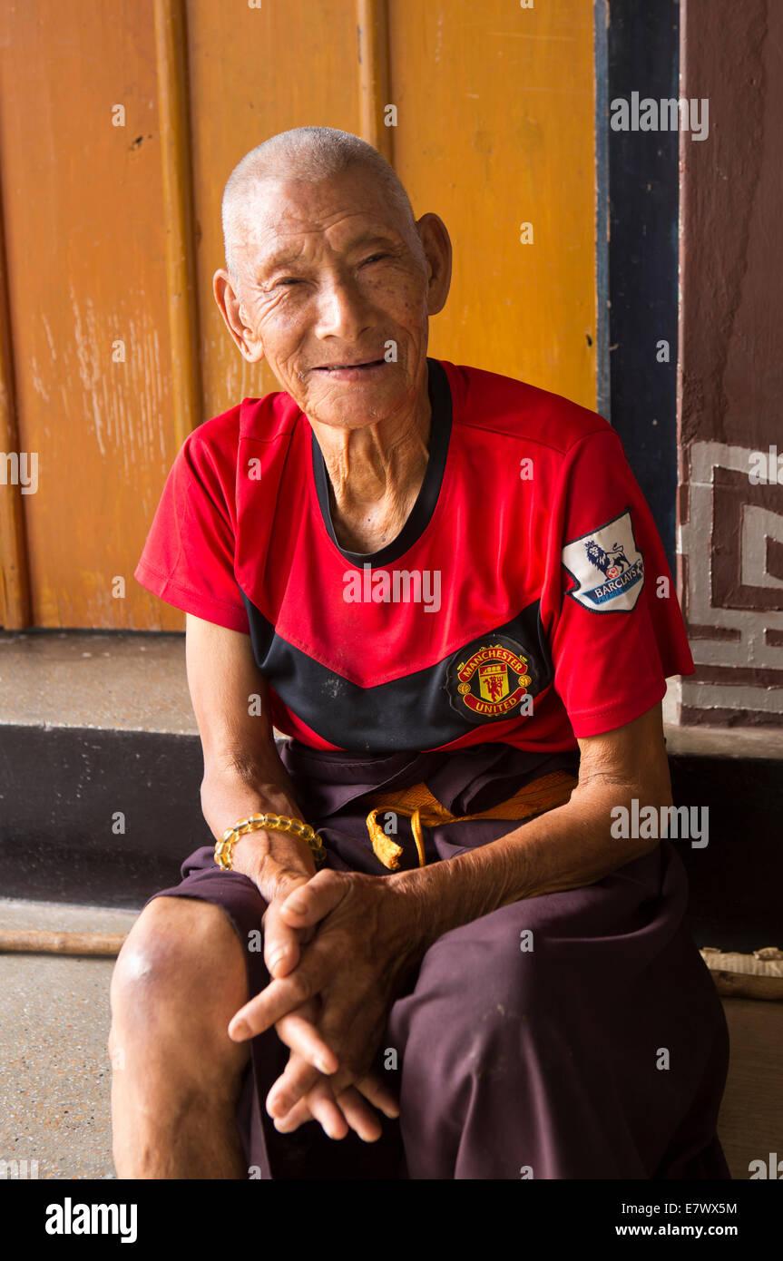 Eastern Bhutan, Trashigang, Rangjung Monastery old monk wearing Manchester United football shirt - Stock Image