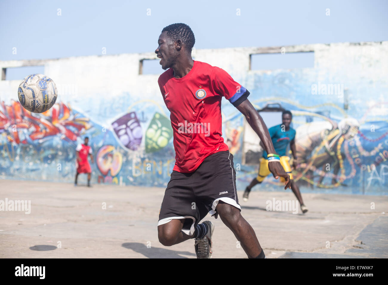 boys playing football with graffiti in background in accra ghana - Stock Image