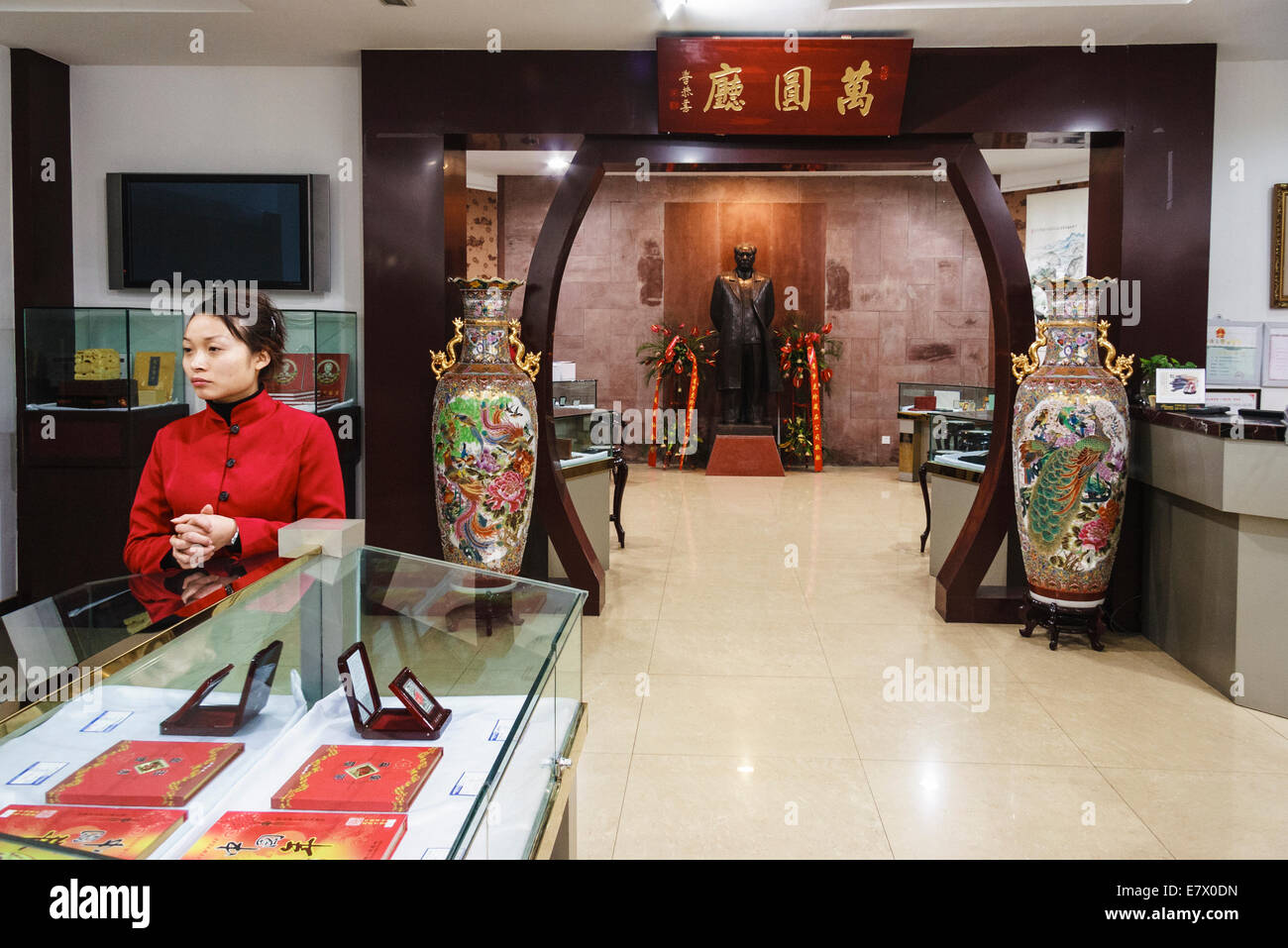Uniformed vendor woman at a luxurious Mao Zedong memorabilia shop with Mao life sized statue in Chengdu, Sichuan, - Stock Image