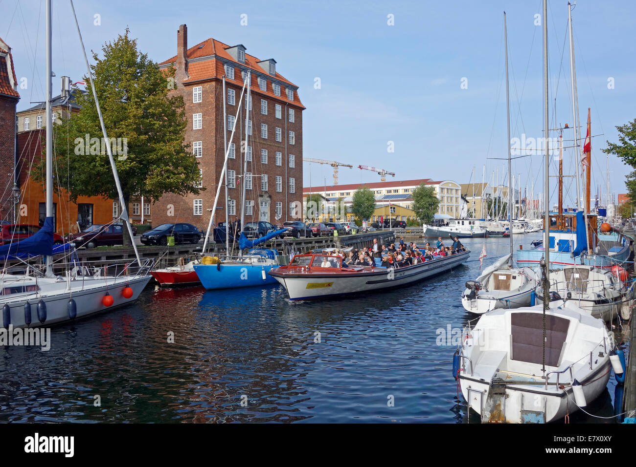 Christianshavn Canal in Copenhagen Denmark with vessels along both quays and canaltours harbour cruise vessel passing - Stock Image