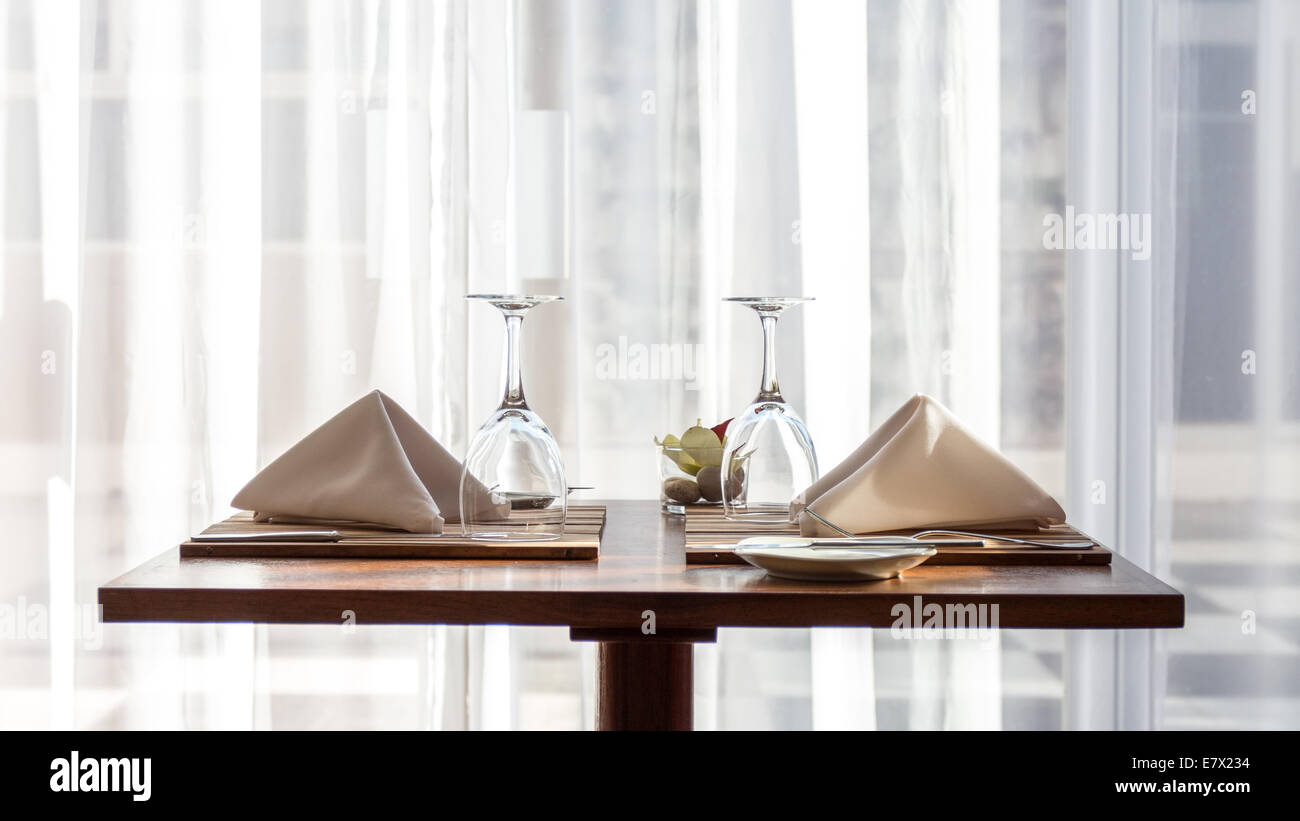 A simple and beautifully arranged table for two, with cloth napkins and wine glasses - Stock Image