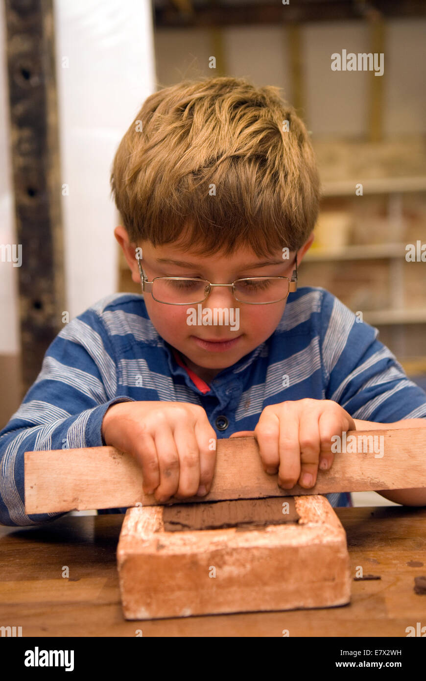 6 year old boy learning brick rolling at a heritage and demonstration day at a local pottery, Farnham, Surrey, UK. - Stock Image