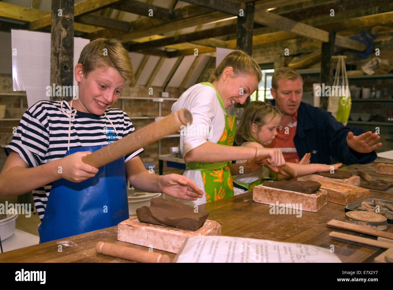 Kids having fun learning brick rolling at a heritage and demonstration day at a local pottery, Farnham, Surrey, - Stock Image