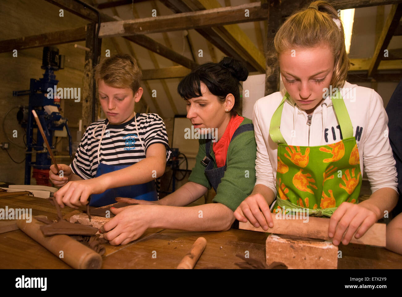 Kids receiving helping hand from tutor (middle) whilst learning brick rolling at a heritage and demonstration day - Stock Image