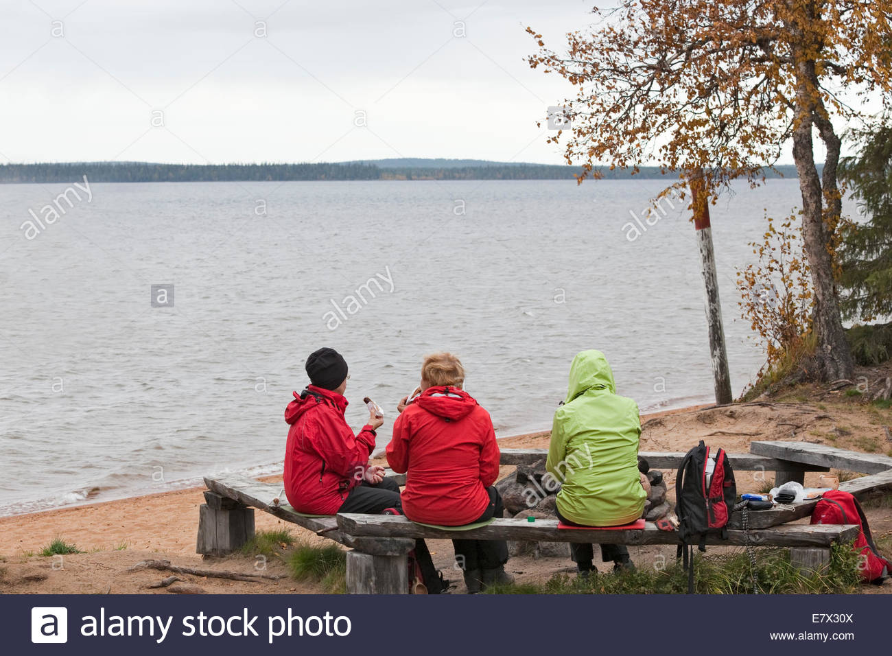 Women enjoying a cup of coffee by a lake in Finnish Lapland - Stock Image
