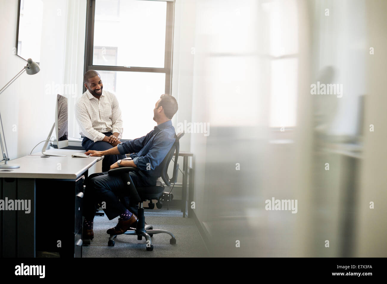 A man leaning back in an office chair talking to a colleague sitting on the edge of the desk. & Office life. A man leaning back in an office chair talking to a ...