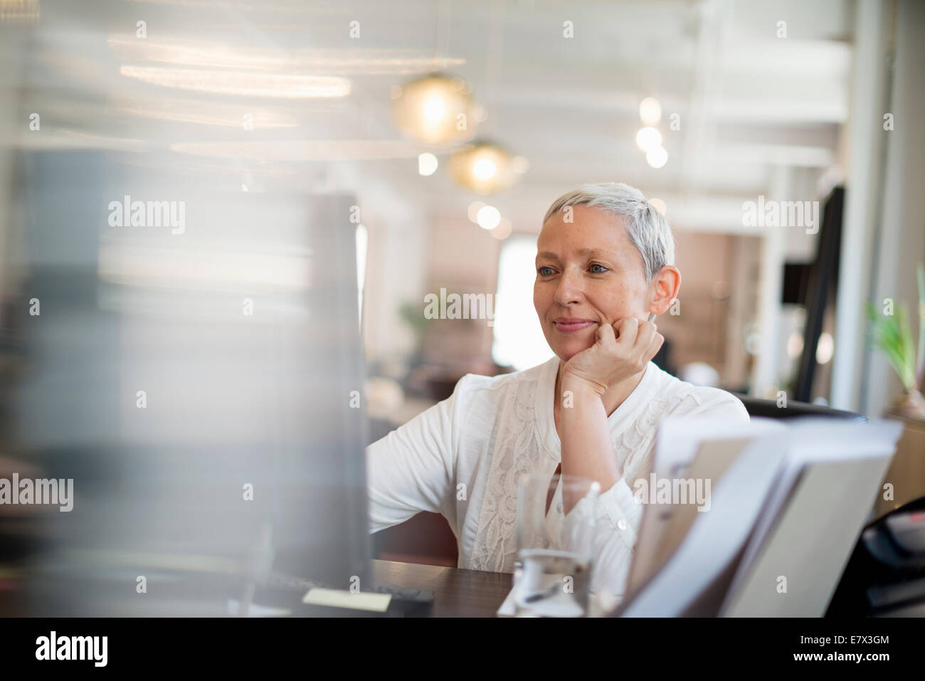 Office life. A woman with her chin resting on her hand using a computer. - Stock Image