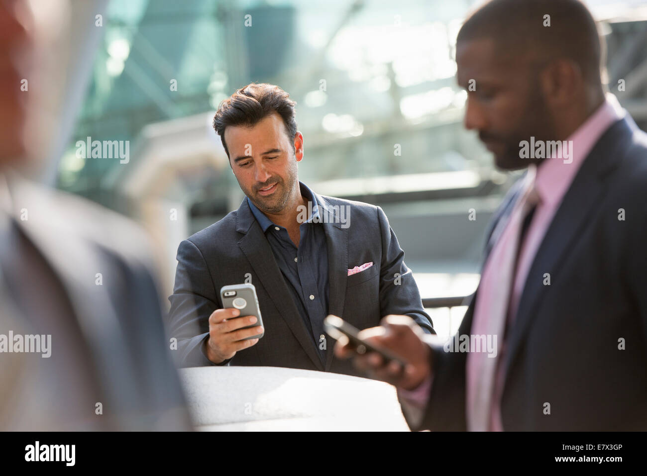 A group of three businessmen, two checking their phones. - Stock Image