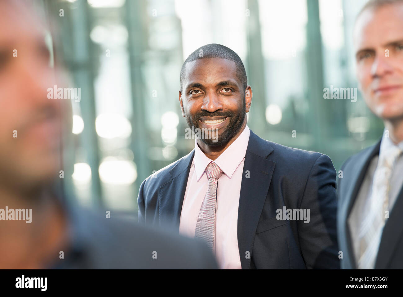 Three people, businessmen outdoors. - Stock Image