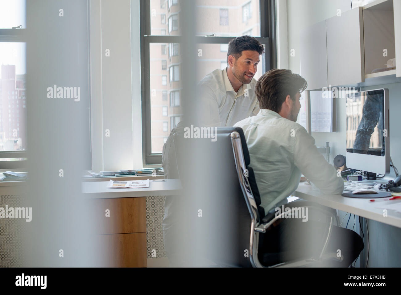 Two men by a computer screen, talking and planning. - Stock Image