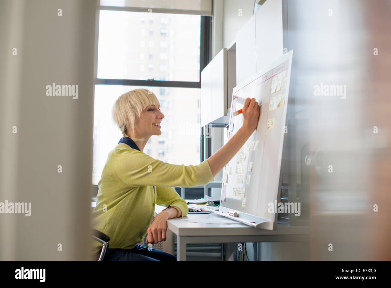 A woman planning using a wall chart and post it notes. - Stock Image