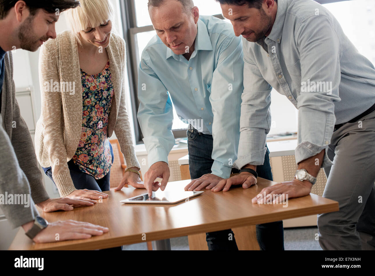 Four people, three man and a woman leaning over a digital tablet on a table. - Stock Image
