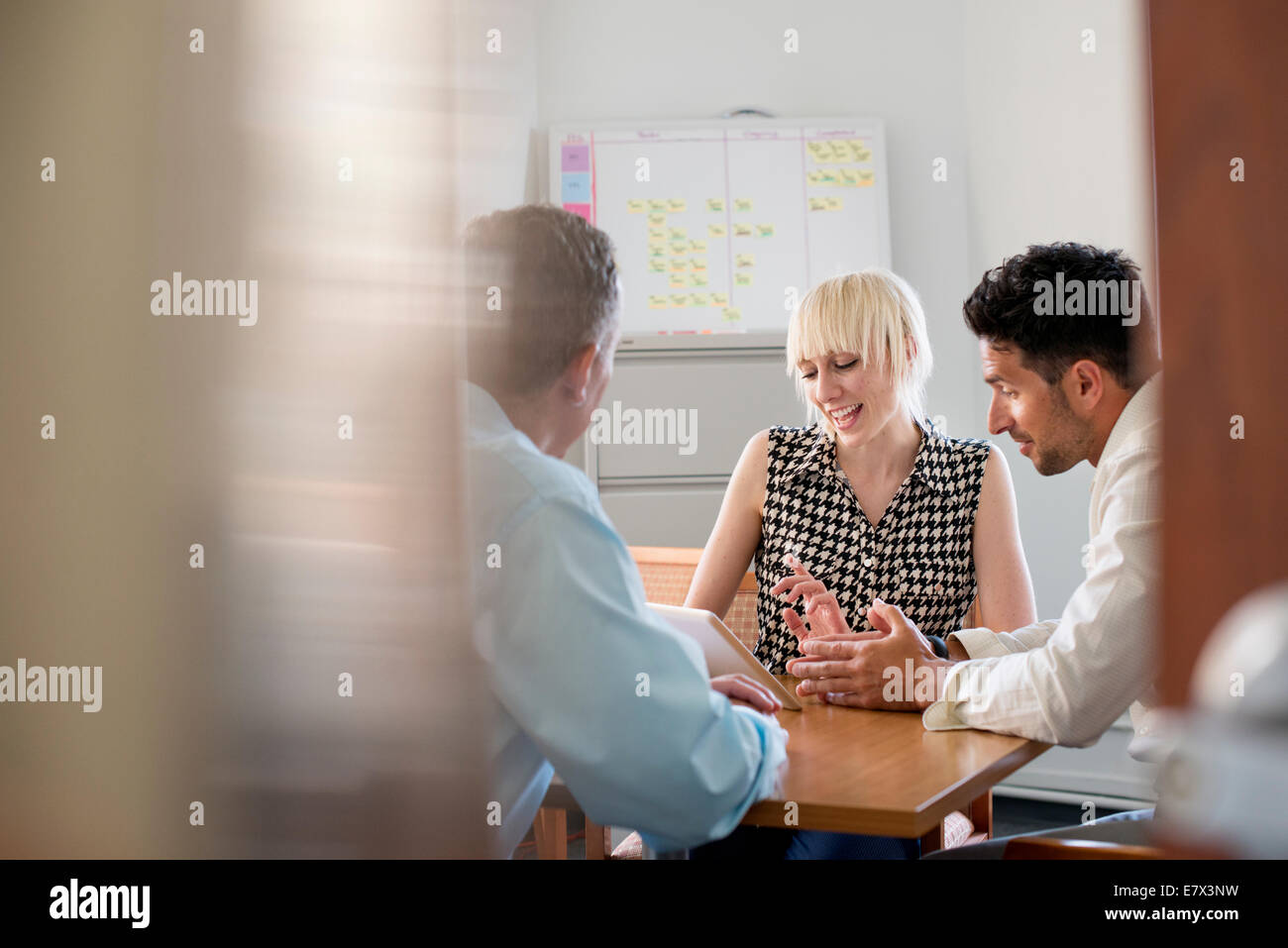 Three business colleagues in an office talking around a table and looking at a digital tablet. Stock Photo