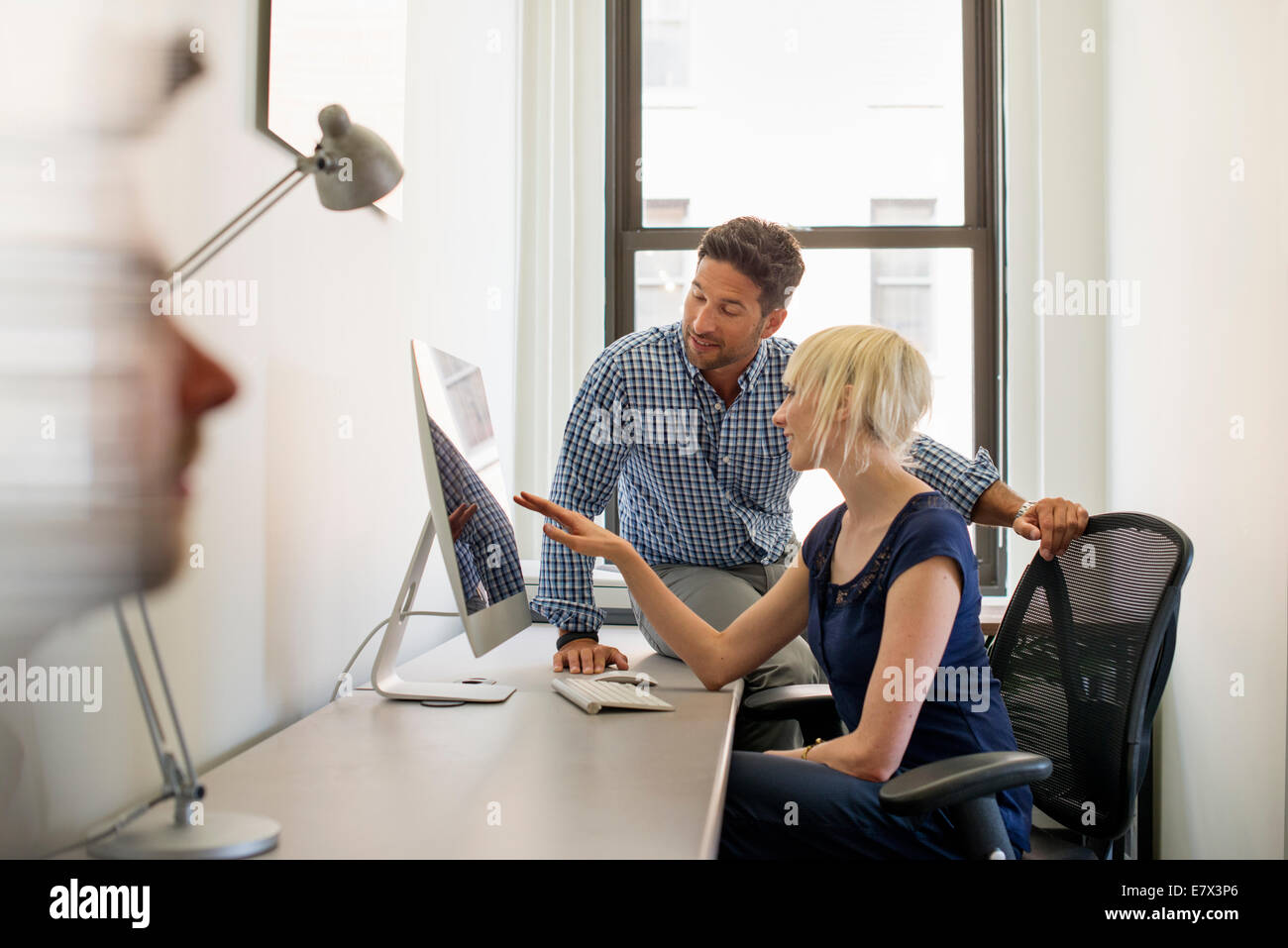 Three business colleagues in an office, two talking and one standing by the door. - Stock Image