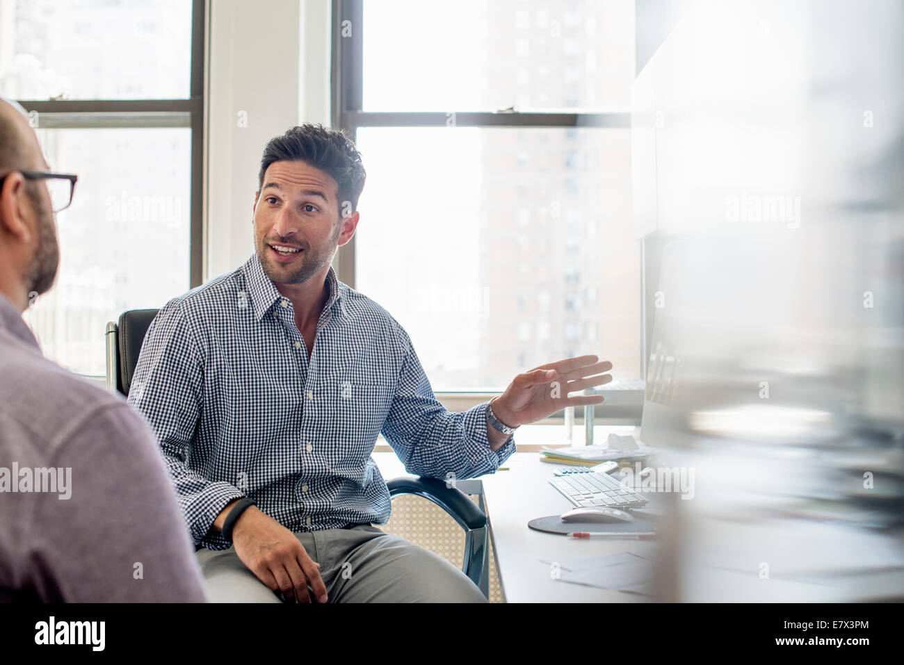 Office life. Two men seated talking and one using his hand to gesture towards a computer monitor. - Stock Image