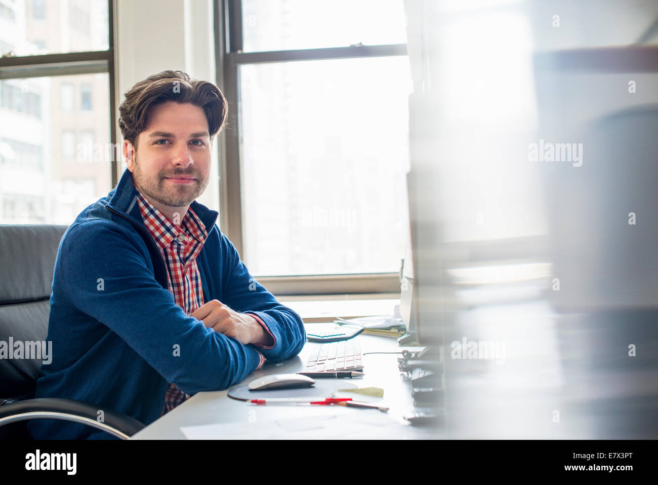 Office life. A man seated with his arms folded at a cluttered desk. - Stock Image