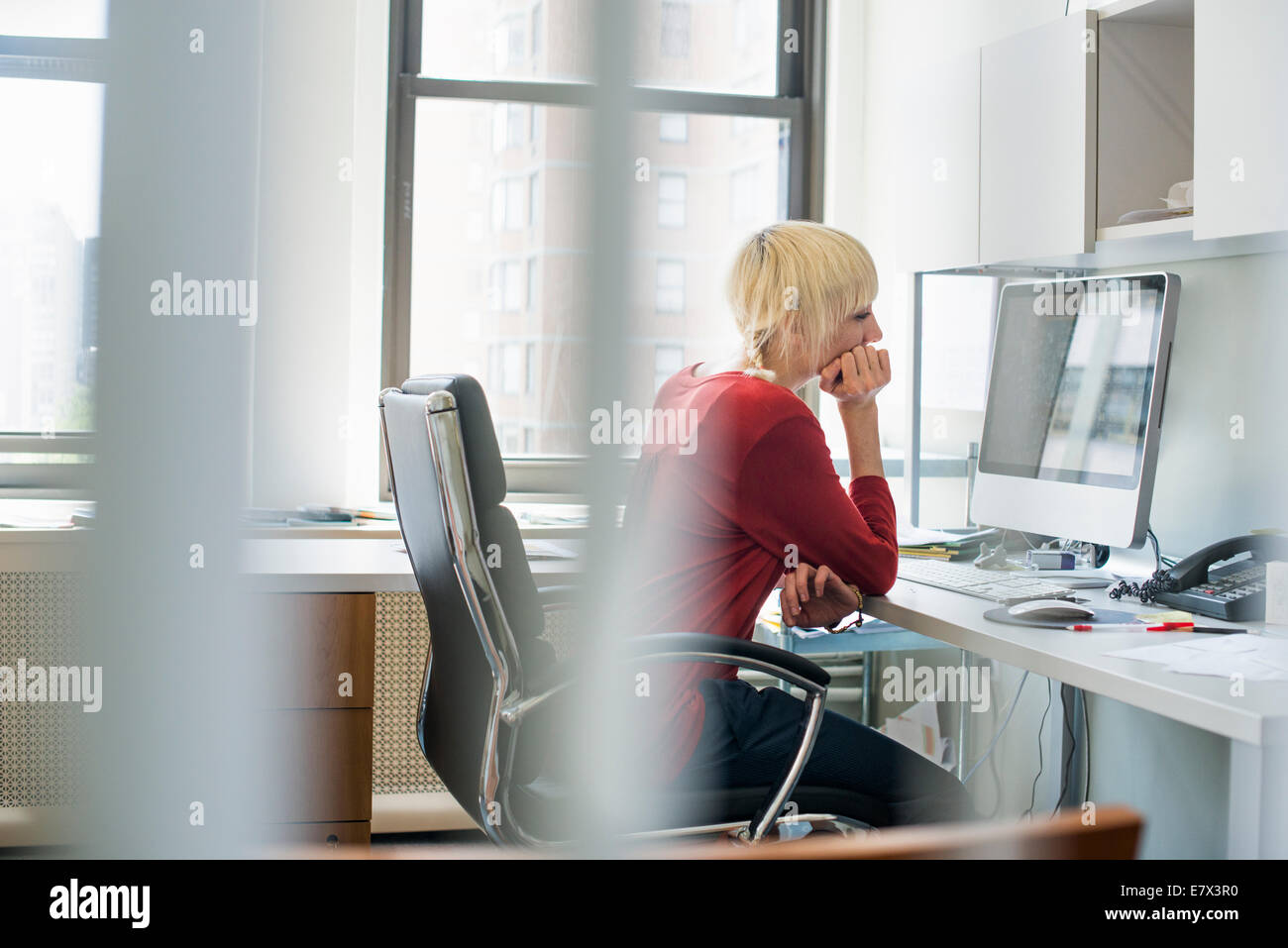 Office life. A woman sitting at a desk using a computer, looking intently at the screen. - Stock Image