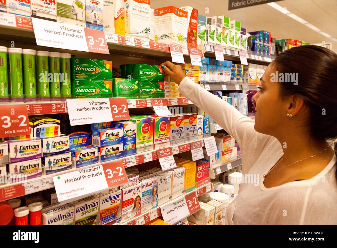 Young woman shopping for / buying vitamins , Waitrose supermarket, Newmarket Suffolk UK - Stock Image