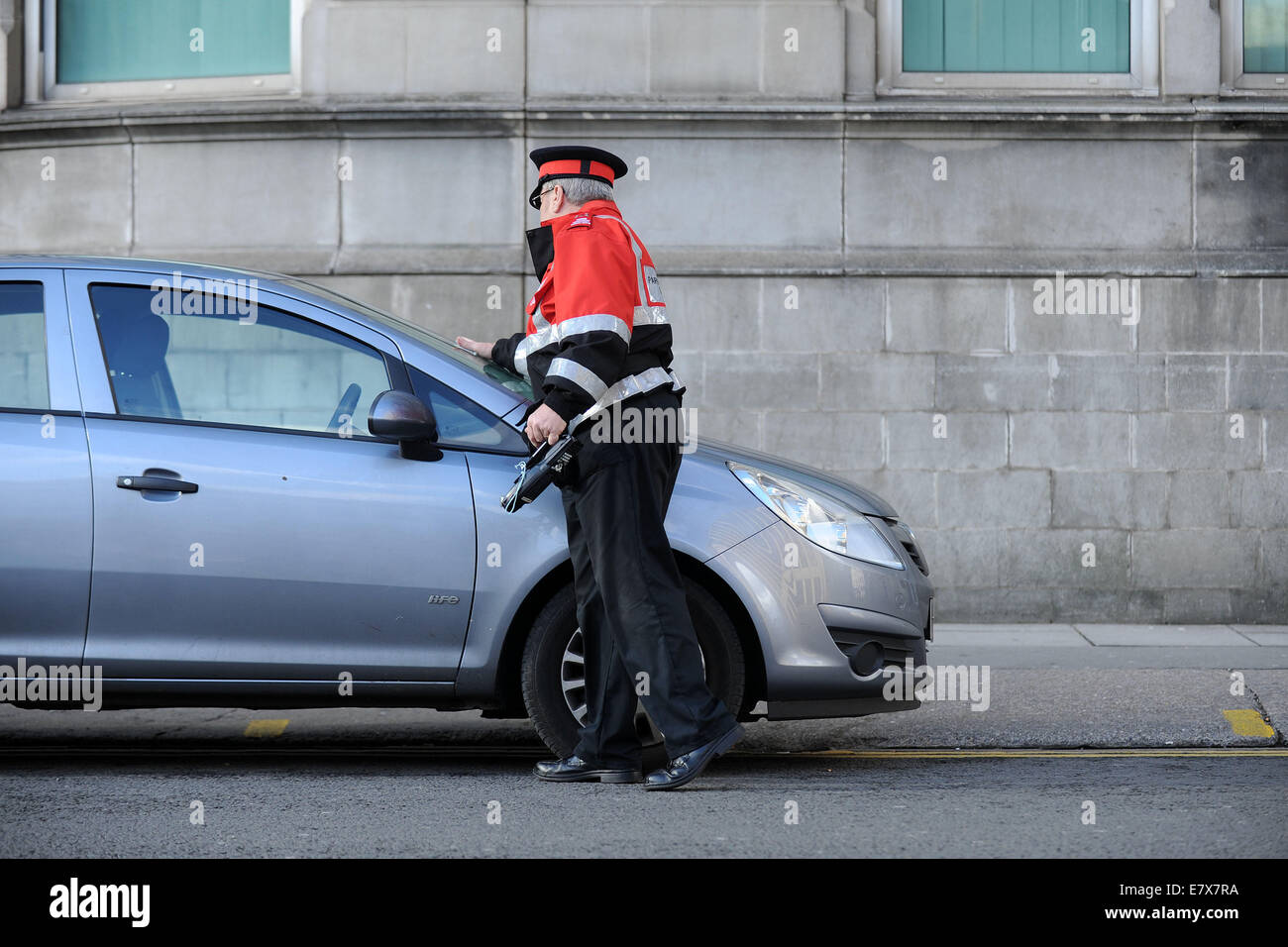 A traffic warden (civil enforcement officer) on patrol issuing parking tickets to illegally parked cars in Cardiff, - Stock Image