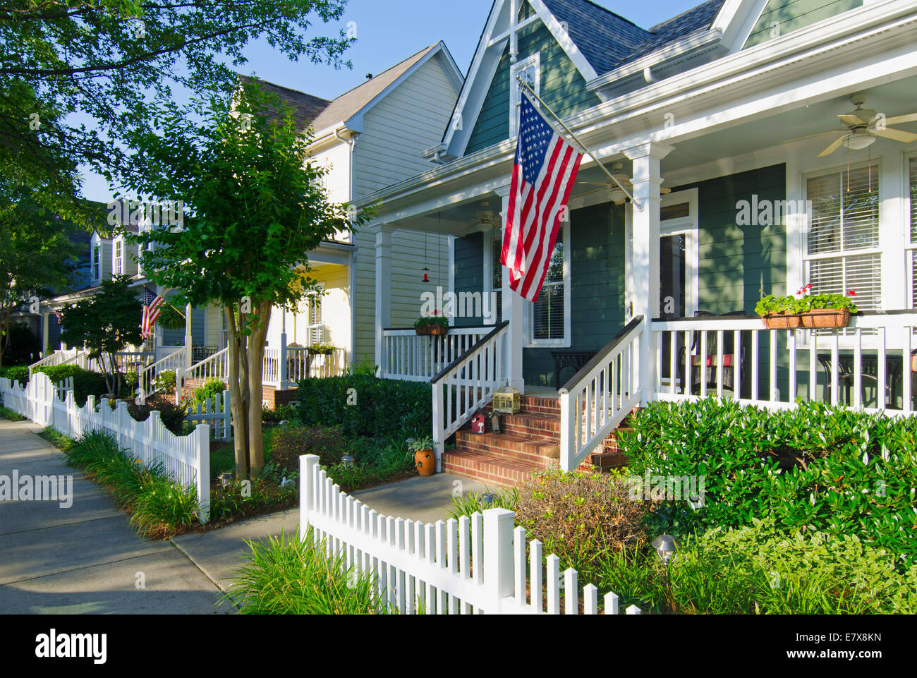 The American Dream Of A Home With A Flag And A White Picket Fence In