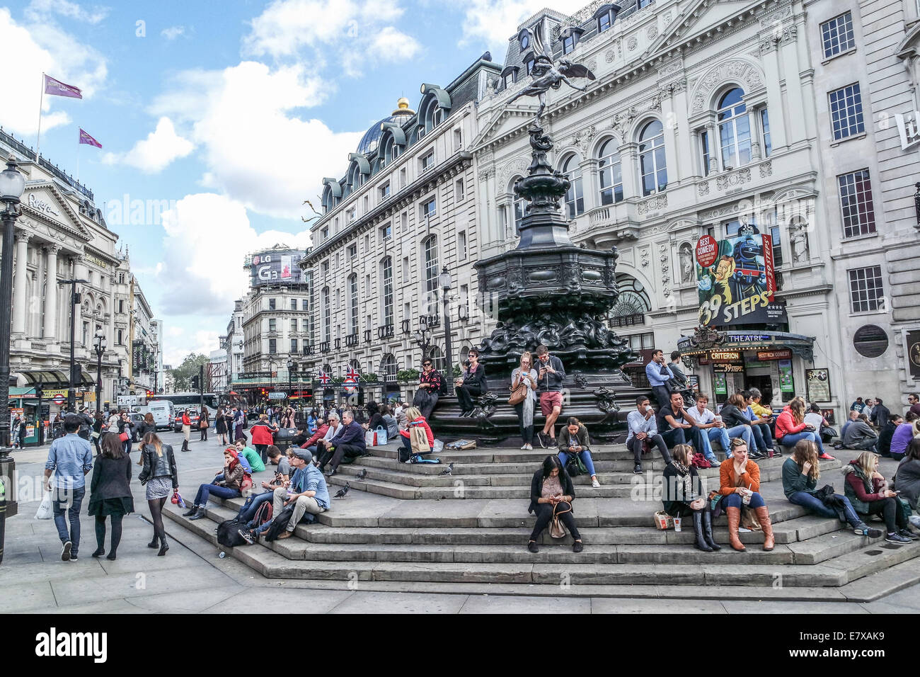 Piccadilly Circus,London, Tourists sit on the Steps of the Eros Statue - Stock Image