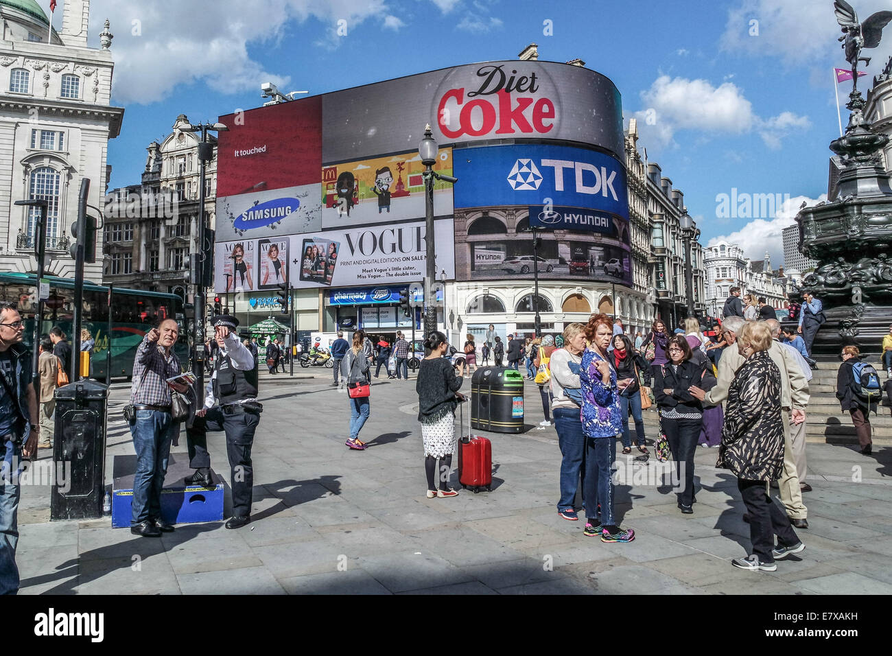Piccadilly Circus, London, A police man gives direction to a tourist - Stock Image
