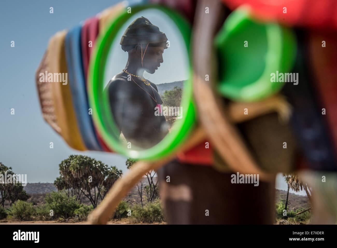 A Samburu warrior is reflected in he fellow shepherd's mirror while out tending their herds. The Samburu warriors - Stock Image