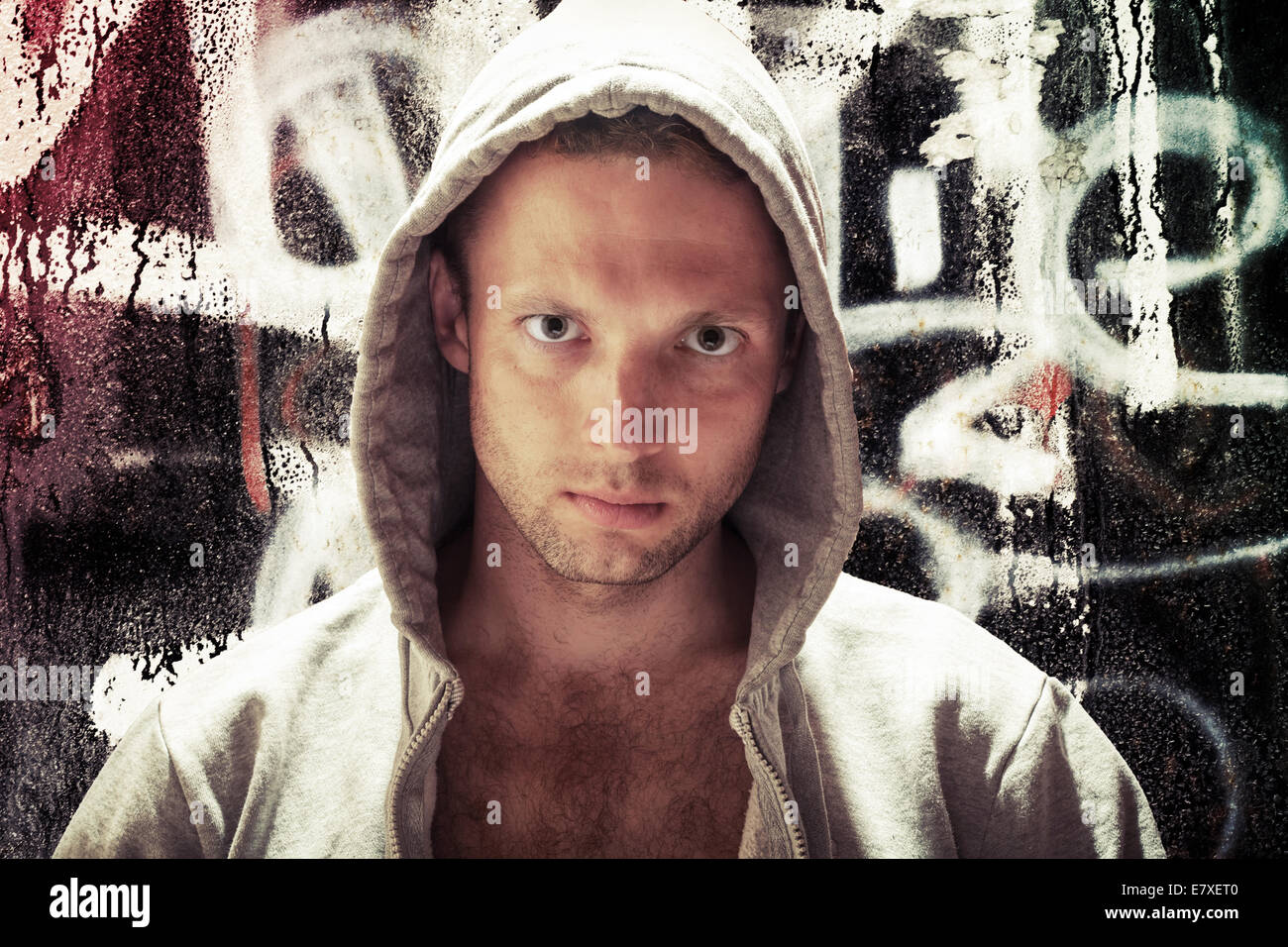 Young Caucasian man in hood, street artist portrait with grungy graffiti wall on background, toned effect - Stock Image