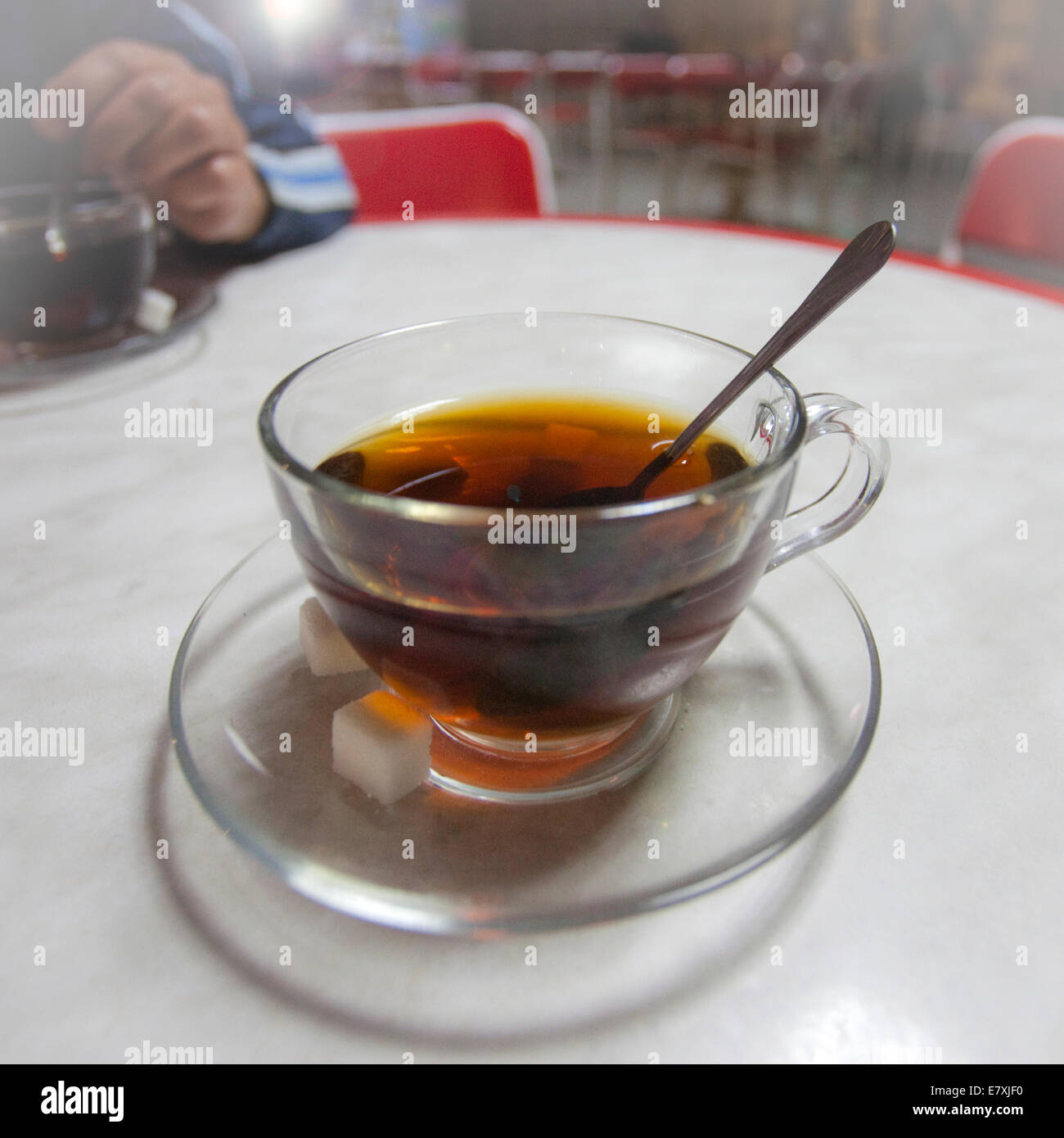 Turkish tea in transparent cup with saucer and spoon and two sugar cubes - Stock Image