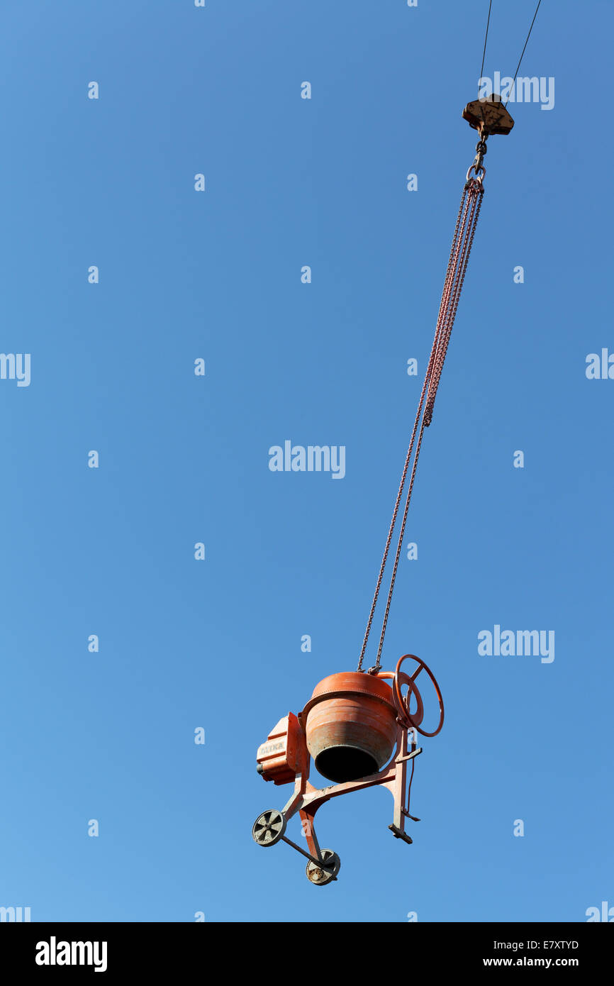 Concrete mixer hanging from a crane, theft protection on a construction site - Stock Image