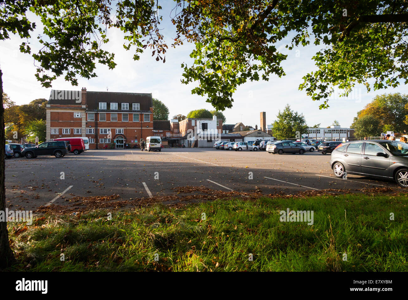 School car park during term time / cars parking in the morning drop off at a primary and secondary school. UK. - Stock Image