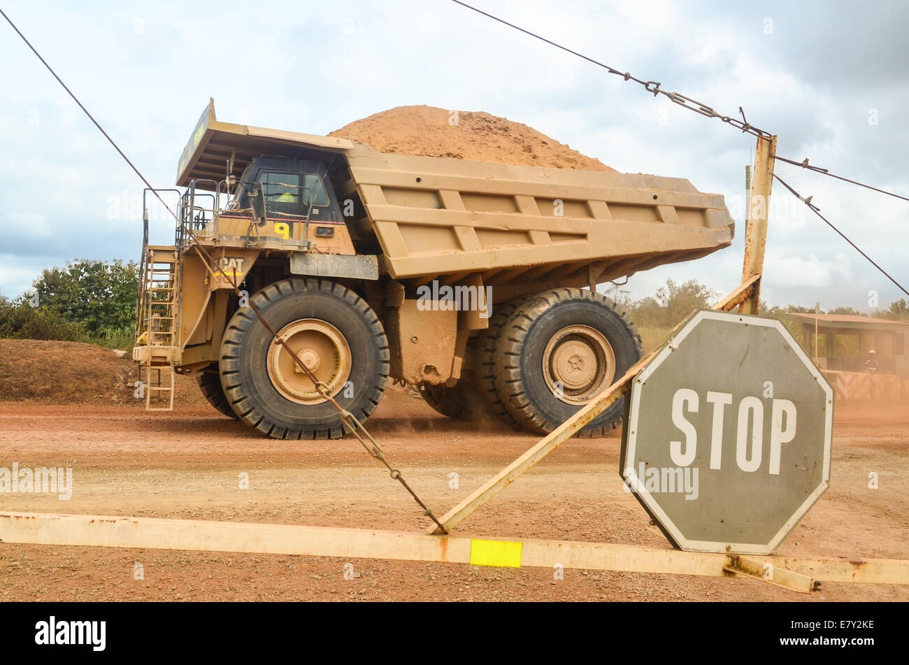 STOP sign, fence and haul truck transporting ore from the Vermont Gold mine to the processing plant , in Ashanti - Stock Image