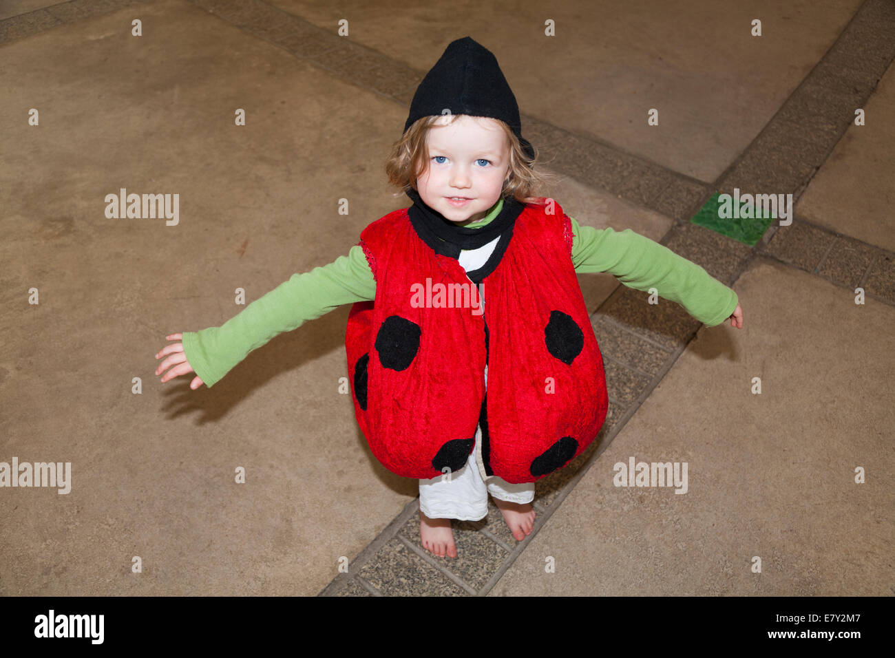 Two 2 year old girl child playing dressing up in fancy costume in the Eden Project 's The Core educational education - Stock Image