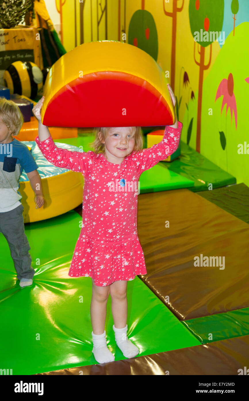 Four 4 year old girl child playing in the soft play area in the Eden Project 's The Core educational education - Stock Image