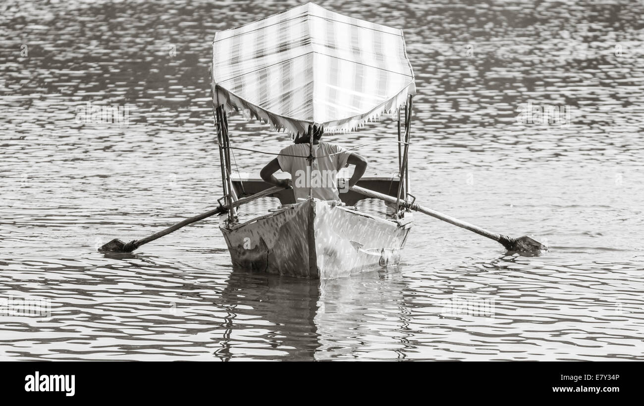 Feb 2, 2014 – Debre Zeit, Ethiopia: Three young men rowing their boat on lake Babugaya, awaiting for tourists  to - Stock Image