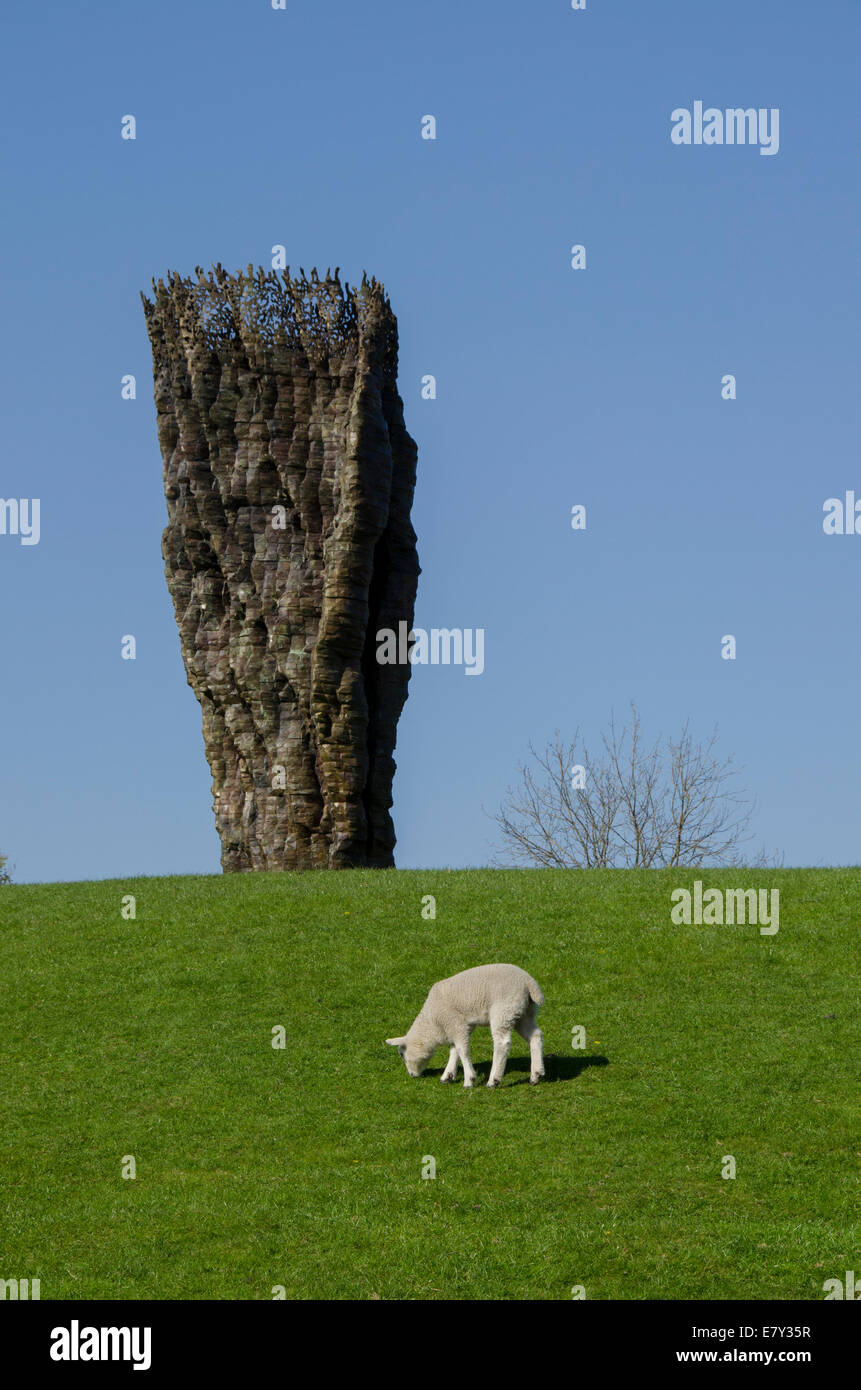Lone sheep or lamb grazes under deep blue sky at foot of 'Bronze Bowl with Lace' by Ursula von Rydingsvard - Stock Image
