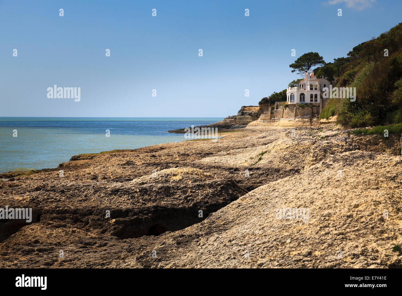 Single imposing house overlooks the calcareous rocks and sea of the Charente Maritime France. - Stock Image